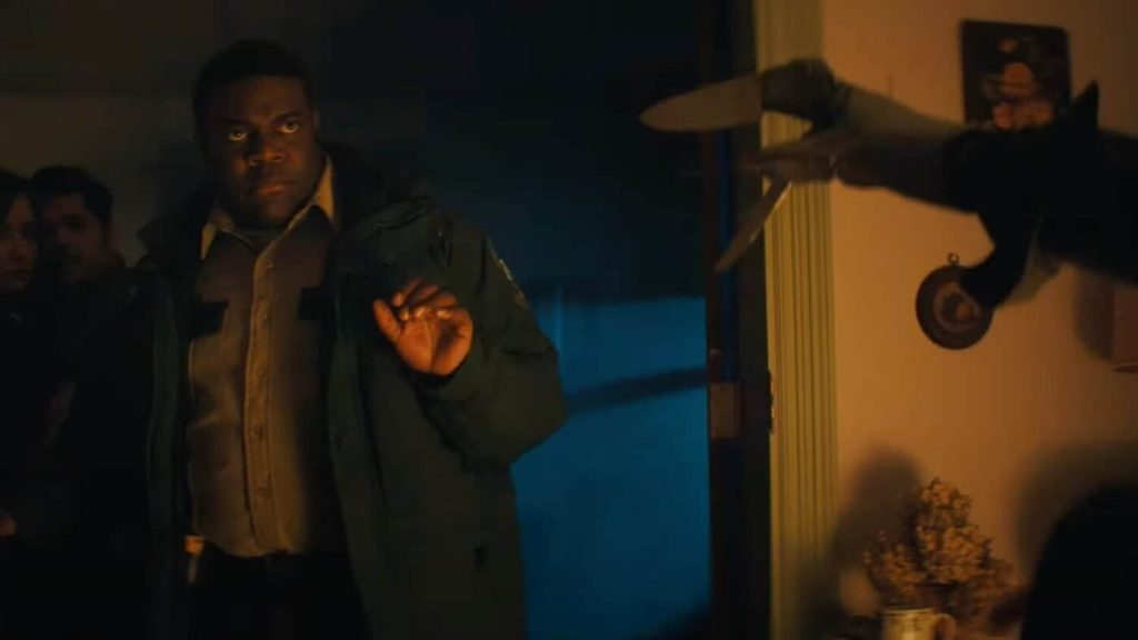 Finn is in a darkly lit room and holds a hand gently in the air to signal calm, his features set seriously. Clawed fingers like Freddy Krueger's can be seen on the edge of the frame
