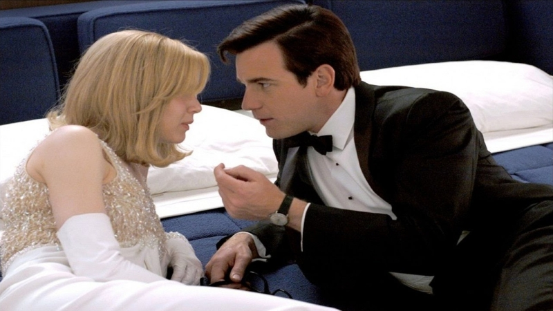 A woman and a man laying on a bed. The woman wears a fancy white dress and gloves and has strawberry blonde hair. The man wears a black tuxedo, seeming to be in the middle of an intense conversation with her.