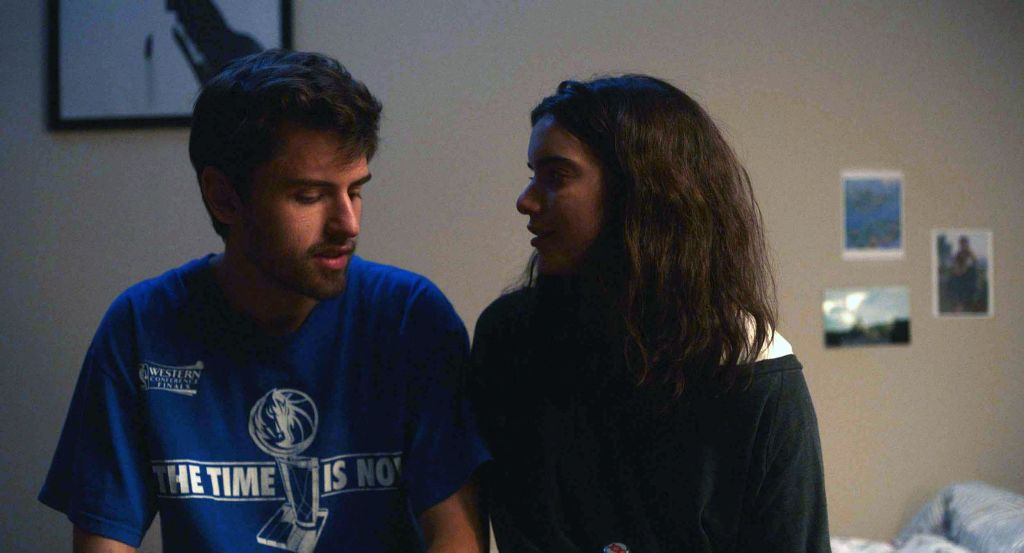 """A young man and a young woman sitting next to one another in a bedroom. The man has dark brunette hair and wears a blue shirt that reads """"THE TIME IS NOW,"""" with an image of a horse head at the top of a basketball net. The woman has medium-length brunette hair, wearing a black off-the-shoulder top while looking at the man. Photographs are seen out of focus on the wall behind her."""