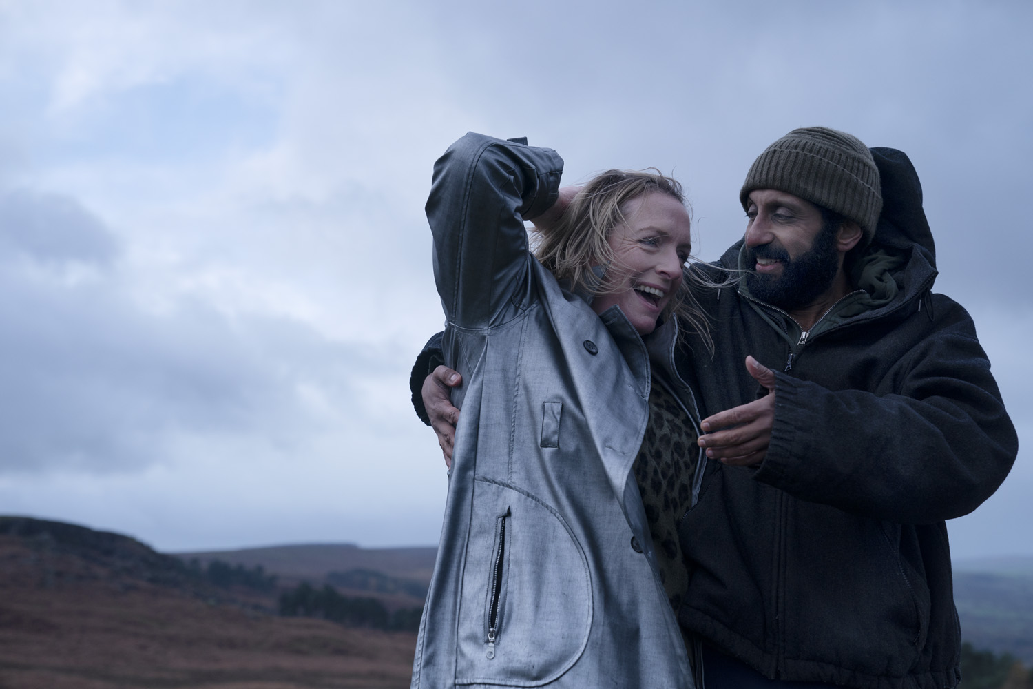 A woman and man outside with hills in the distance behind them. The woman has windswept blonde hair and is smiling, while wearing a leopard print top and bluish-grey jacket. The man has a beard and wears a beanie and dark coat, while looking at the woman and smiling.