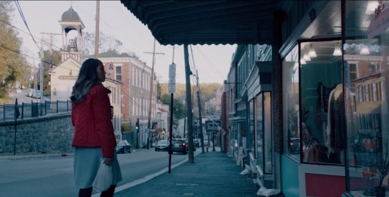 An Asian girl in a red coat and grey skirt standing on a city street. She appears to be looking into a shop window.