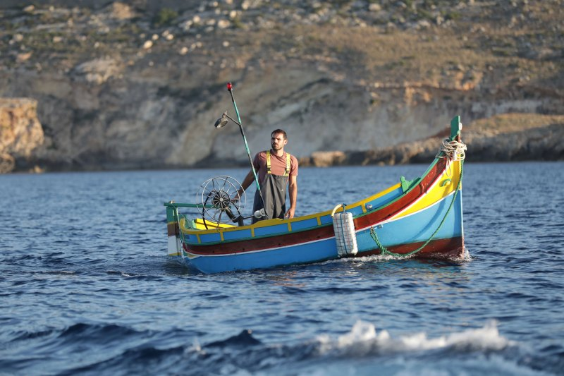 A man stands on a colourful fishing boat in the middle of the ocean. He wears a maroon shirt and overalls, and the boat is blue, yellow, and red.